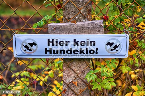 istock Dog excrement prohibited. Letters with Hier kein Hundeklo! Means No dog toilet here 1168967388