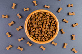 dog food in a wooden bowl and snack like bones on black background, flat lay