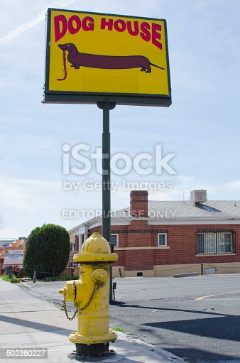 Albuquerque, United States - May 18, 2014: The Dog House Restaurant is a legendary eatery along historic Route 66 in Albuquerque, New Mexico.  Its sign is ironically placed behind a yellow fire hydrant.