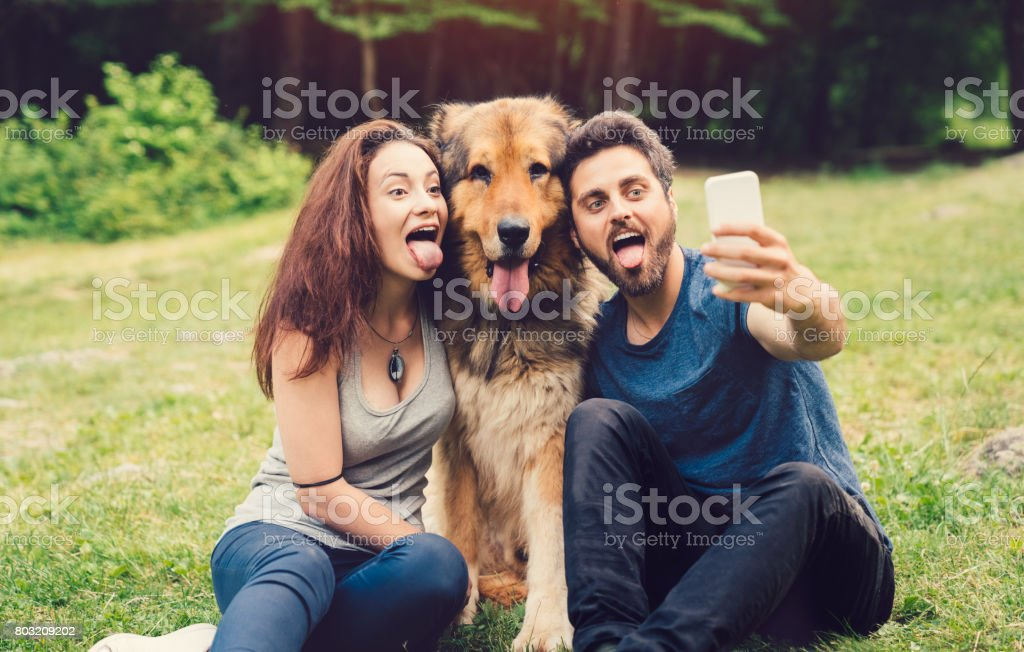 Dog owners taking selfie with dog in the city park stock photo