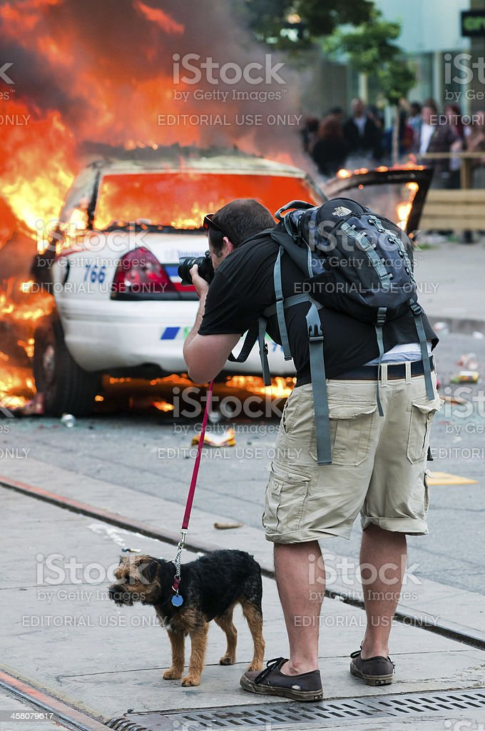 "Dog walker photographing a fire ""Toronto, Canada - June 26, 2010: A photographer take pictures of a burning police car on Queen Street West in Toronto while walking his dog on a leash.  Several police cars were lit on fire in the city's downtown core in protest of the G20/G8 summits in June 2010."" Adult Stock Photo"