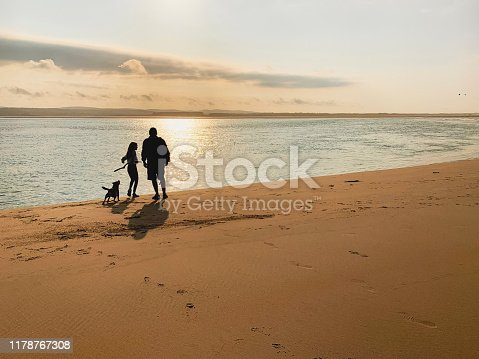 Rear view silhouettes of a father and daughter walking their dog along a beach at dusk. The girl is holding a stick ready to through.