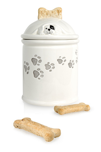 Dog treats in a jar and two dog bones on the outside.