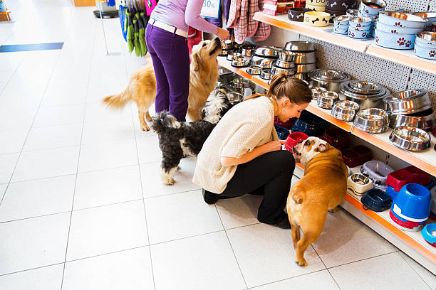 Dogs and his owners in pet store buying new bowl - Photo