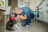 Owner and his boston terrier hugging