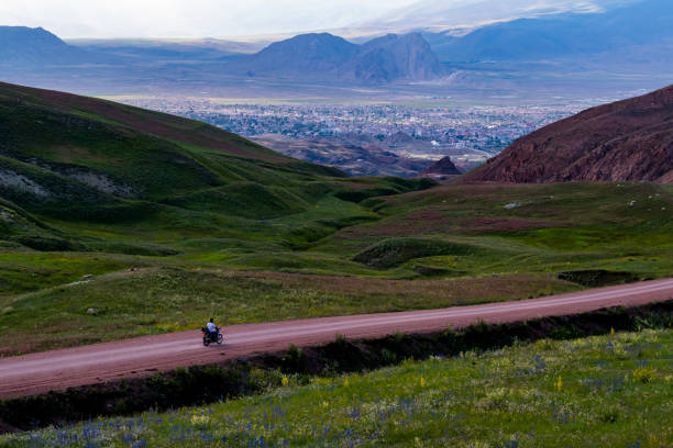 Dogubayazıt, Turkey, Middle East: a man from behind driving a motorcycle in the breathtaking landscape on the dirt road on the plateau around Mount Ararat, Agri Dagi, with rocky peaks, hills, grassland and flowers near Ishak Pasha Palace stock photo