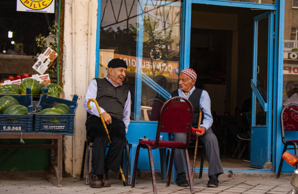 Dogubayazıt, Turkey, Middle East: local men smiling and sitting on chairs upon a sidewalk in Dogubayazıt, a town 15 km southwest of Mount Ararat in the easternmost district of Turkey bordering Armenia and Iran stock photo