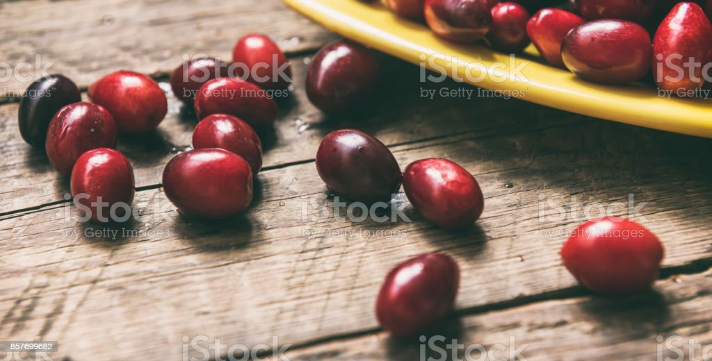 Dogwood edible fruit in bowl on wooden surface stock photo