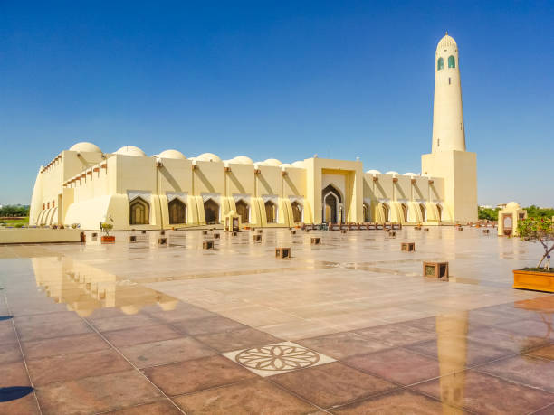 Doha Grand Mosque State Grand Mosque with a minaret reflecting on marble pavement outdoors. Doha mosque in Downtown, Qatar, Middle East, Arabian Peninsula. Morning daylight shot. Sunny day with blue sky. grand mosque stock pictures, royalty-free photos & images