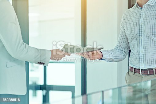 Shot of a businessman handing a document to a colleague
