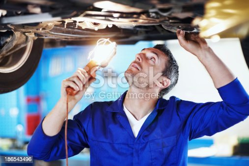 Automotive mechanic peering underneath a car while holding a lamp