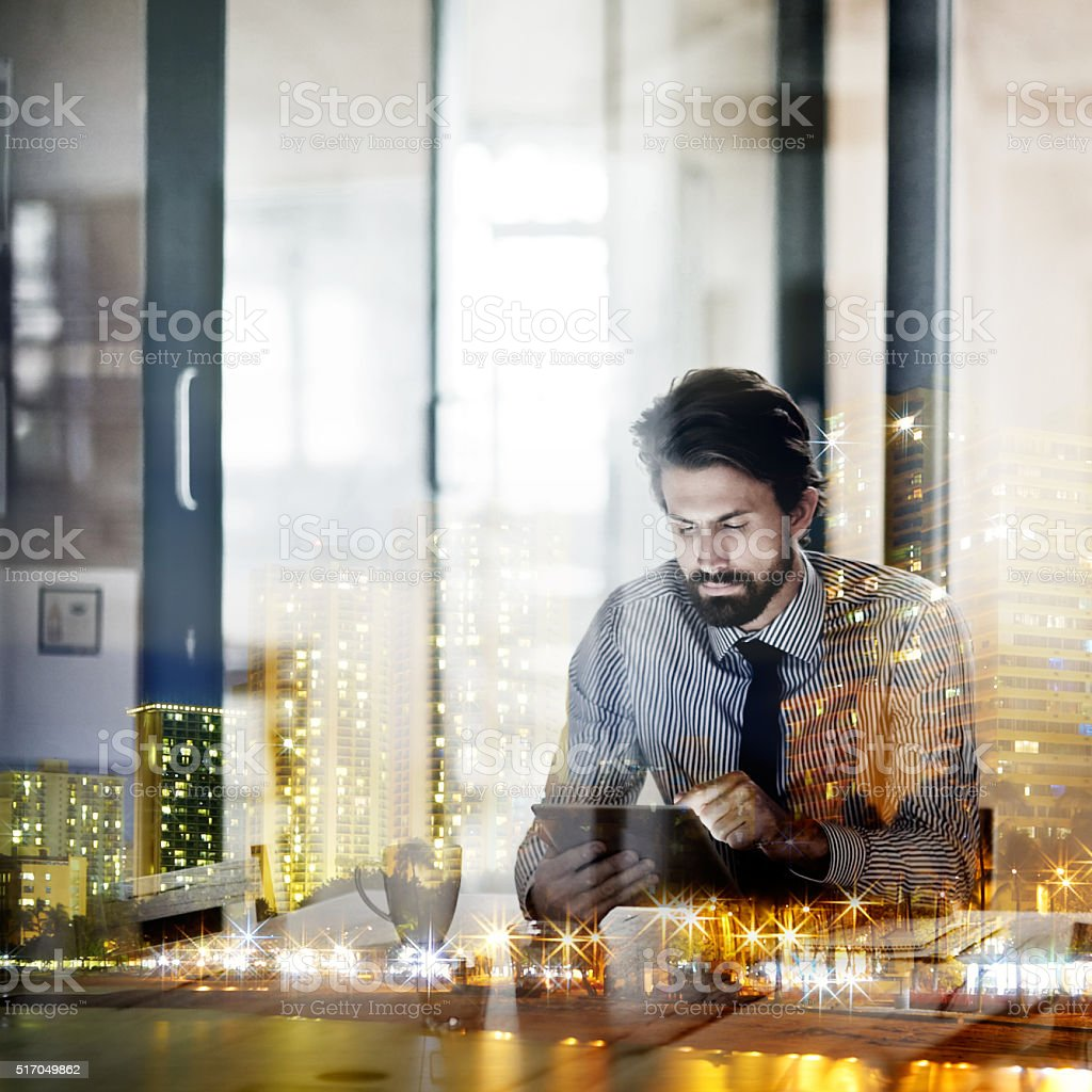 Multiple exposure shot of a young businessman working in an office...