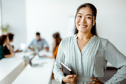 Confident young Asian businesswoman standing smiling at the camera in a boardroom with colleagues in the background