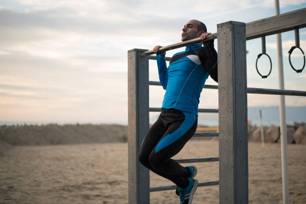 doing chin-ups on the beach - man city exercise abs foto e immagini stock