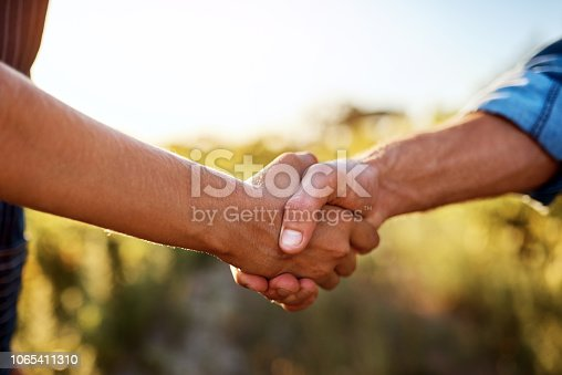 Cropped shot of an unrecognizable man and an unrecognizable woman shaking hands on a farm