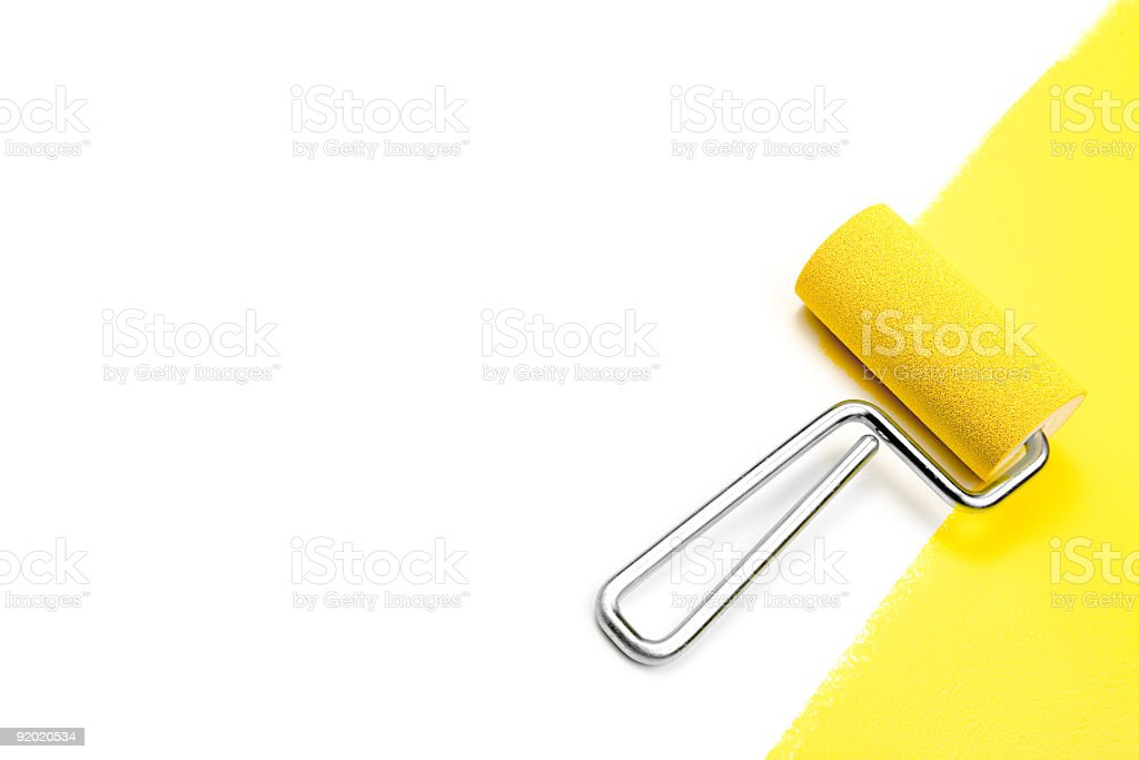 Doing home improvement by painting a white wall yellow stock photo