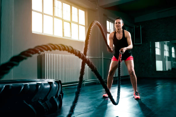 Doing intense hard gym training with rope at gym stock photo