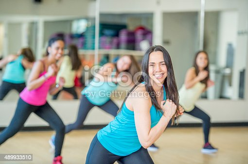 A group of women are dancing together in a fitness class at a gym studio. They are wearing fitness clothing and are smiling while looking at the camera.