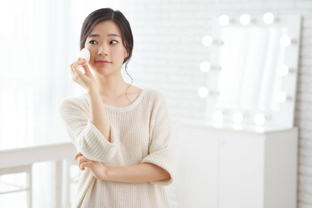 Doing make-up Pretty Korean girl applying make-up with white sponge korean ethnicity stock pictures, royalty-free photos & images