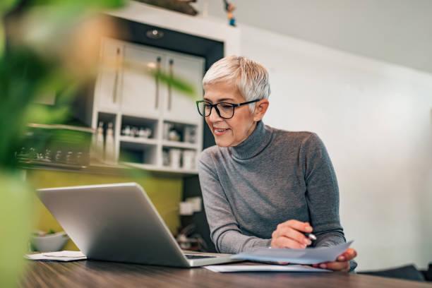 Haciendo papeleo en casa. Mujer mayor mirando la computadora portátil y sosteniendo el documento de papel, retrato. - foto de stock