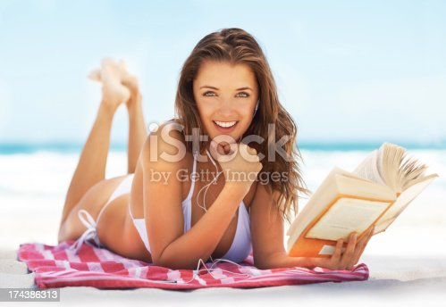 Young woman lying on the beach in her bikini and listening to some music while reading