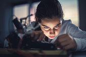 Young girl working on robotics arm.