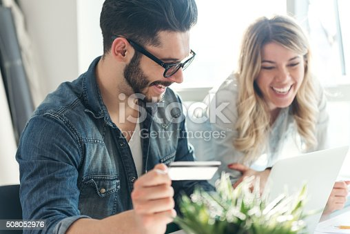 A happy young couple relaxing together and making some online purchases.
