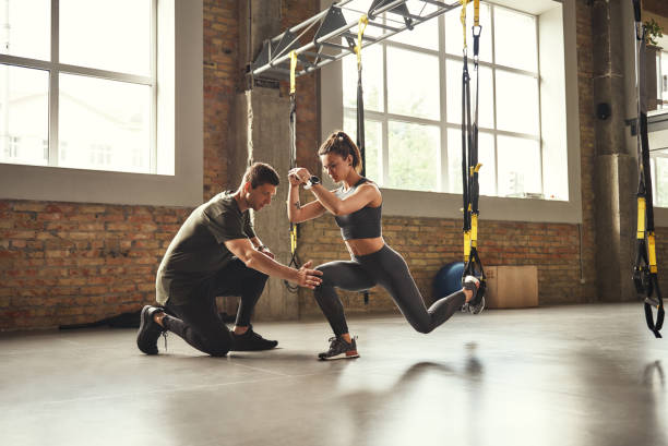 het doen squat oefening. zelfverzekerde jonge personal trainer toont slanke atletische vrouw hoe squats te doen met trx fitness bandjes tijdens het trainen in de sportschool. - personal trainer stockfoto's en -beelden