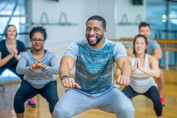 Doing Squats A group of adults are taking a fitness class together. They are doing squats and smiling at the camera. exercise class stock pictures, royalty-free photos & images