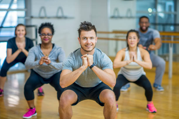 Doing Squats A group of adults are taking a fitness class together. They are arranged in rows and are smiling at the camera while doing squats. exercise class stock pictures, royalty-free photos & images