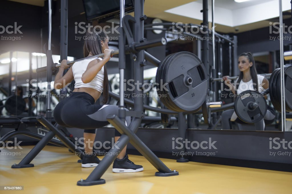 Doing squats with barbell in a gym stock photo