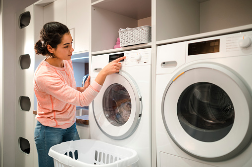 Woman doing her laundry while at home in the Northeast of England. She is pressing a button on her washing machine.