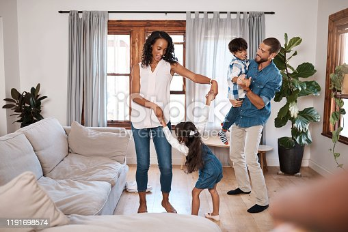 Shot of a family of four dancing together at home