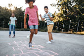 Multi-ethnic group of kids playing hopscotch outside, jumping and  having fun