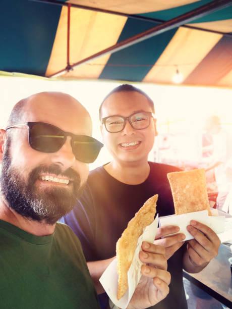 dois amigos comendo pastel na barraca da feira, portugal domingo de manhã. - pastel de feira - fotografias e filmes do acervo