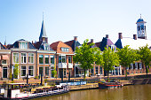 Dokkum, Friesland, Netherlands: Traditional canal-side houses in a row in Dokkum, one of the 11 Friesian historic cities. Canal and boats in the foreground.