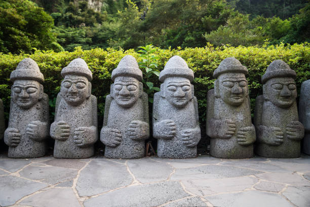 Dol Hareubang statues in a row in green forest, Seogwipo, Jeju Island, South Korea Dol Hareubang statues in a row with hats and hands on belly in green forest, Seogwipo, Jeju Island, South Korea seogwipo stock pictures, royalty-free photos & images