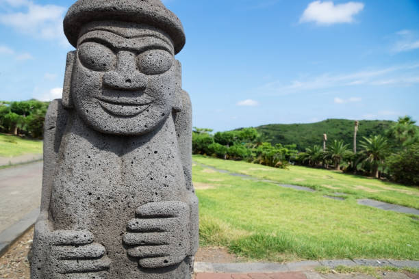 Dol Harubang statue in green grassland at Yongmeori Beach, Sanbang-ro, Jeju Island, South Korea stock photo