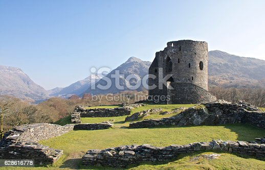 Wide shot of Dolbadarn Castle Keep on a clear summers day showing the staircase and surrounding ruins overlooked by mountains and lush green grass.