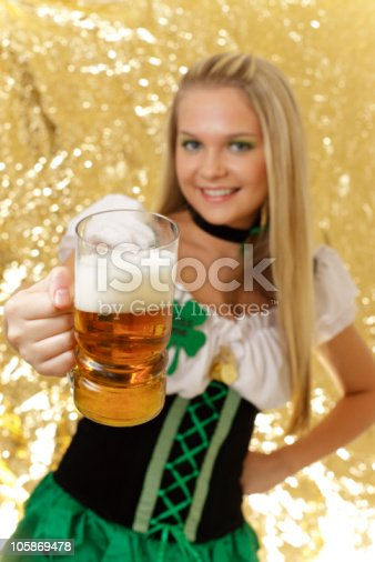St. Patrick's Day young woman dressed in Irish clothing offering a beer mug. (focus on mug)