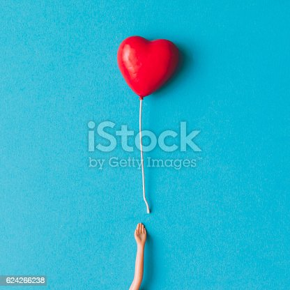 istock Doll hand with heart shaped baloon. Minimal concept. Flat lay. 624266238