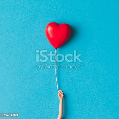 istock Doll hand with heart shaped baloon. Minimal concept. Flat lay. 624266324