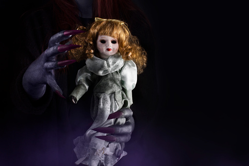 Doll in witch's hands