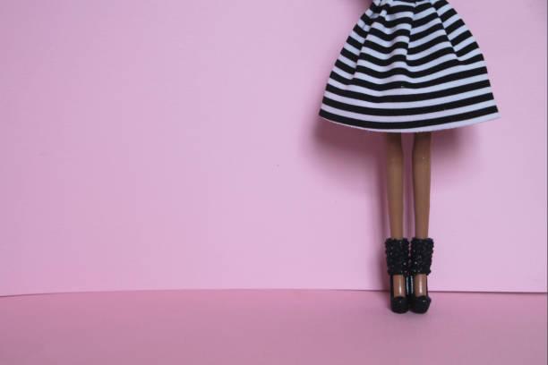 puppe beine und gestreiften rock auf rosa hintergrund - damen rock pink stock-fotos und bilder