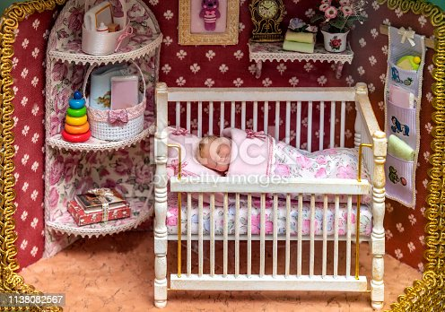 Doll miniature with the baby in the crib and the interior of the room.The picture shows the author's doll. Author Olga Pavlycheva, shooting was done in the doll gallery of Olga Pavlycheva in the town of Myshkin, Russia. Property release attached