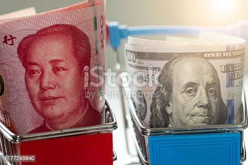 istock US dollar and China Yuan banknote on shopping cart.Its is symbol for tariff trade war crisis between United States of America and China which the biggest economic country in the world. 1177245940