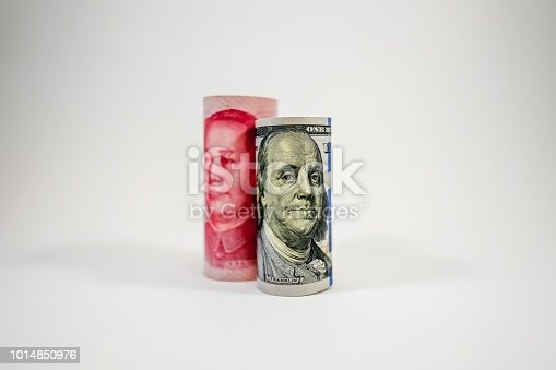 istock US dollar and China Yuan banknote roll stand up on white background. 1014850976