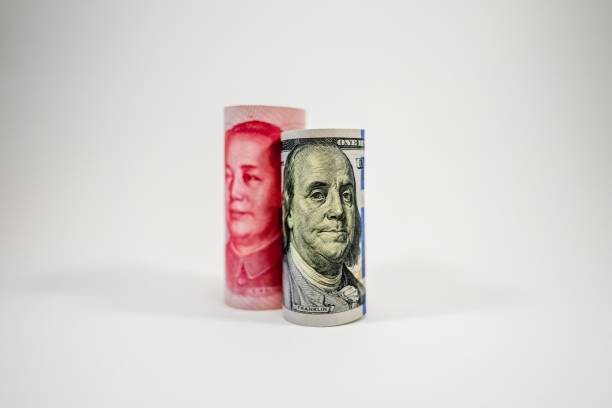 US dollar and China Yuan banknote roll stand up on white background. US dollar and China Yuan banknote roll stand up on white background. Both countries increase tax barrier for protect domestic goods in war trade economy. chinese currency stock pictures, royalty-free photos & images