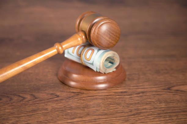 dólar y juez sobre la mesa - indemnización compensación fotografías e imágenes de stock