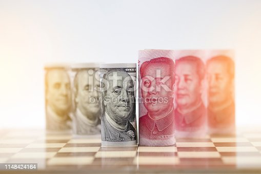 istock US dollar and Yuan banknote on chessboard for trade war between United States and China which both countries battle by increase tax barrier of import and export product. Government and business. 1148424164